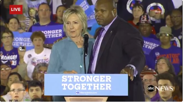Secret Service agents walk on stage at Hillary Clinton rally